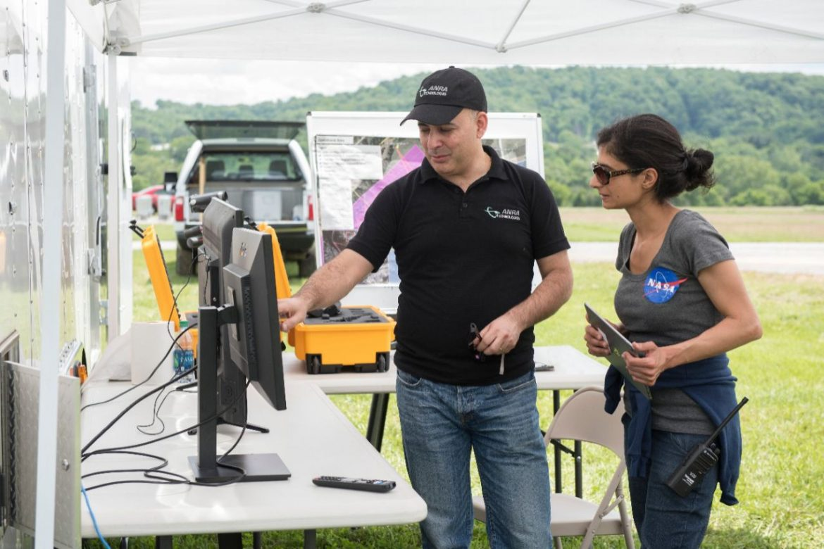 Amit Ganjoo, left, CEO of ANRA Technologies, and Arwa Arweiss, NASA's Unmanned Traffic Management National Campaign coordinator, watch as the flight paths of unmanned aircraft participating the tests appear on screens displaying a traffic-management software user interface